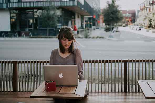 A woman sitting on a wooden bench facing a laptop