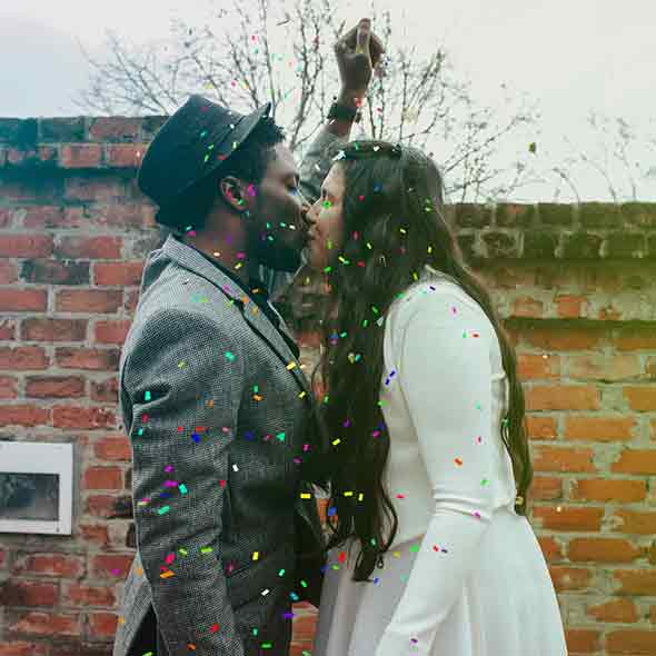 An interracial couple kissing with confetti falling around them.