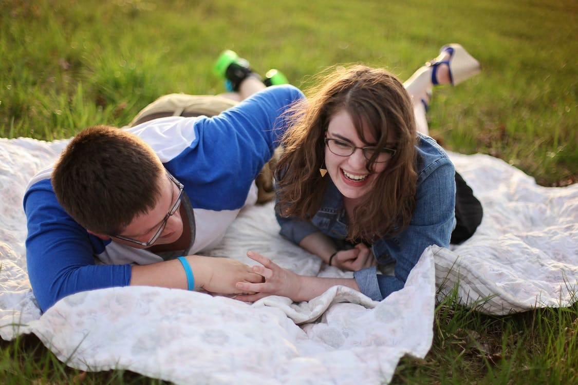 A couple laughing while holding hands on the blanket on top of the grass.