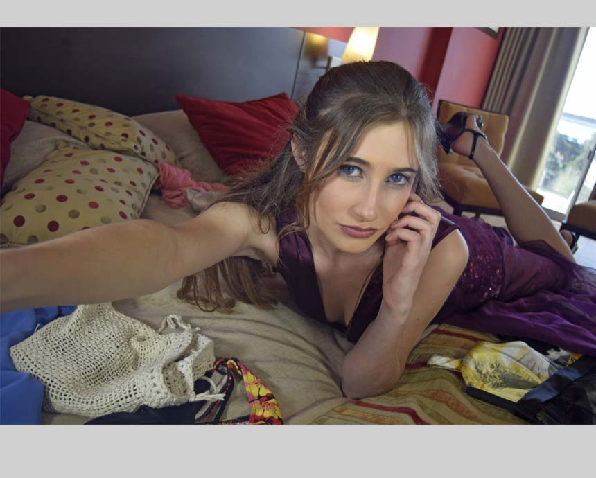 woman holding a selfie lying on bed